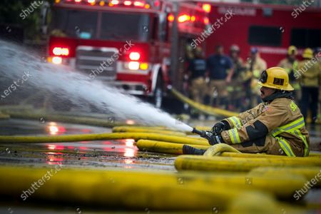 San Bernardino County firefighter Sergio Mora uses a water hose to douse a massive warehouse fire on 2200 block of West Lugonia Avenue in Redlands. 2200 block of West Lugonia Avenue