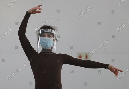 Cape Town City Ballet company dancer Gabrielle Fairhead wears a face mask and shield does exercises as the company returned for their first day back at work after more than two months in lockdown in Cape Town, South Africa, . The dancers have been training at home due to strict lockdown regulations that have been implemented in a bid to prevent the spread of coronavirus
