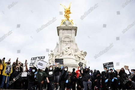 Demonstrators hold placards backdropped by the Victoria Memorial, outside Buckingham Palace, during a Black Lives Matter march in in London, as people protest against the killing of George Floyd by police officers in Minneapolis, USA. Floyd, a black man, died after he was restrained by Minneapolis police while in custody on May 25 in Minnesota