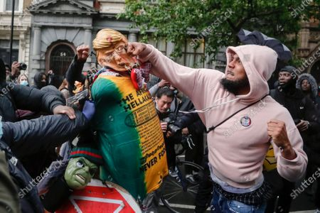 Demonstrator punches a puppet depicting US President Donald Trump during a Black Lives Matter march in London, as people protest against the killing of George Floyd by police officers in Minneapolis, USA. Floyd, a black man, died after he was restrained by Minneapolis police while in custody on May 25 in Minnesota