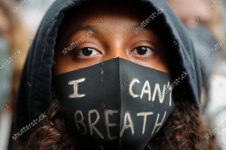 Girl wears a face mask during a Black Lives Matter rally in Parliament Square, in London, as they protest against the killing of George Floyd by police officers in Minneapolis, USA. Floyd, a black man, died after he was restrained by Minneapolis police while in custody on May 25 in Minnesota