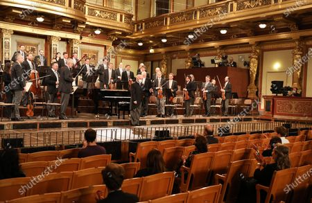 Stock Photo of Conductor Daniel Barenboim (C) and the Vienna Philharmonic Orchestra greet the audience at the golden hall of Vienna's Musikverein in Vienna, Austria, on June 5, 2020.   The first concert of the Vienna Philharmonic Orchestra was held on Friday after a COVID-19 lockdown at Vienna's Musikverein. Only 100 guests are allowed in the concert hall because of government regulations.