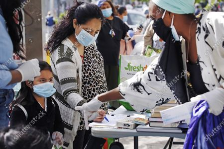 Stock Image of Volunteer Sequaña Williams-Hechavarria, right, instructs youngster Jade Suarez to look beneath the table for books as Jade's mother, Maria, signs up for assistance and free supplies provided by Sistas Van during the coronavirus outbreak at a busy Bushwick intersection in the Brooklyn borough of New York, . Sistas Van was originally launched by the nonprofit Black Women's Blueprint to help survivors of sexual and reproductive violence and physical abuse. But during the coronavirus, the women's network has pivoted to delivering badly-needed resources to black and Hispanic communities, which have had some of the city's highest rates of contagion and death toll of the fast-spreading virus