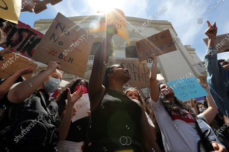 Protesters hold placards and raise their fists as they gather at a Black Lives Matter rally in Tunis, Tunisia, 06 June 2020.  Protesters rally out of solidarity with the Black Lives Matter movement in the wake of the death in police custody of George Floyd in the United States.