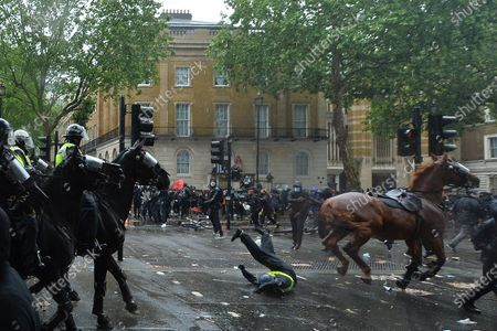 A policewoman falls off a horse as police try to clear a demonstration against racism on Whitehall, London.