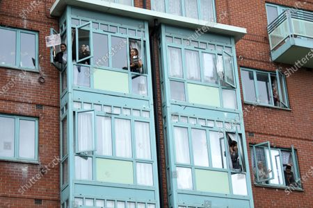 People cheer out their windows as an anti-racism protest passes below along Vauxhall Bridge Road, London.