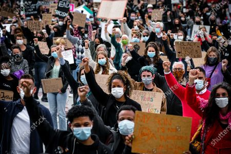Demonstrators wear face masks as they raise their fists while taking part in a massive protest at the Stadhuisplein square in Eindhoven, The Netherlands, 06 June 2020. The anti-racism demonstration was held to condemn the killing of George Floyd, a 46-year-old African-American man who died on 25 May after being detained by police officers in Minneapolis (Minnesota), and to express solidarity with the Black Lives Matter-led protests currently taking place throughout the USA.