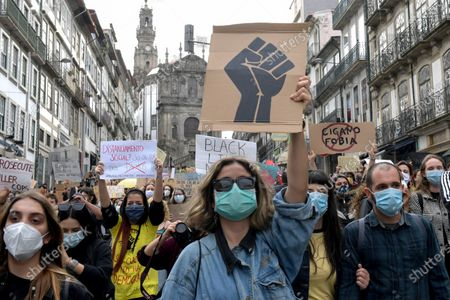 Protesters wear face masks as they take part in an anti-racist and anti-fascist demonstration in Porto, northern Portugal, 06 June 2020. The march was held to condemn the killing of George Floyd, a 46-year-old African-American man who died on 25 May after being detained by police officers in Minneapolis (Minnesota), USA, and to express solidarity with the Black Lives Matter-led protests currently taking place throughout the US. Video footage recorded by bystanders appeared to show police officer Derek Chauvin forcefully kneeling on Floyd's neck for several minutes while the latter pleaded that he couldn't breathe and three other officers passively looked on. Outrage over this new alleged killing of an unarmed black man at the hands of US police has spread across the country and abroad, giving rise to many spontaneous protests around the globe and some riots in major American cities.