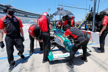 Tony Kanaan's team make adjustments to his car as he participates during practice for the IndyCar auto race at Texas Motor Speedway in Fort Worth, Texas