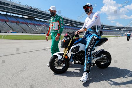 Tony Kanaan, left, and Graham Rahal laugh as they talk on pit road during qualifying for an IndyCar auto race at Texas Motor Speedway in Fort Worth, Texas