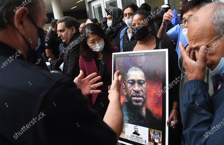 LAPD Chief Michael Moore, left, talks with community leaders outside police headquarters after a candle light vigil for George Floyd Friday.