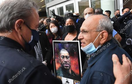 LAPD Chief Michael Moore talks with community leaders outside police headquarters after a candle light vigil for George Floyd Friday.