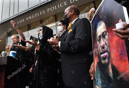 LAPD Chief Michael Moore raises a lit candle outside police headquarters during a vigil for George Floyd Friday.