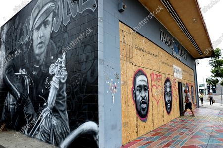 Stock Picture of Mural of Marlon Brando, left, beside where artists have memorialized George Floyd, left to right, who died while in-custody of the Minneapolis Police, Ahmaud Arbery, shot and killed by two white males, Breonna Taylor, was fatally shot by Louisville Metro Police Department officers, and was found hanged in a jail cell after being arrested for a traffic violation, with murals and street art in Venice.