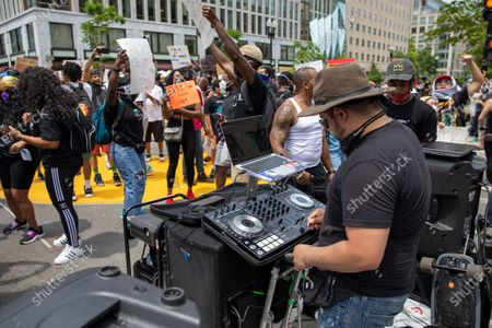 DJ Chris Legend plays music during a march against police brutality and racism