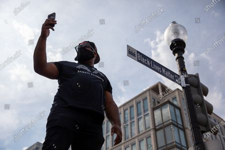 A protester takes a photo in front of the new Black Lives Matter Plaza street sign during a march against police brutality and racism