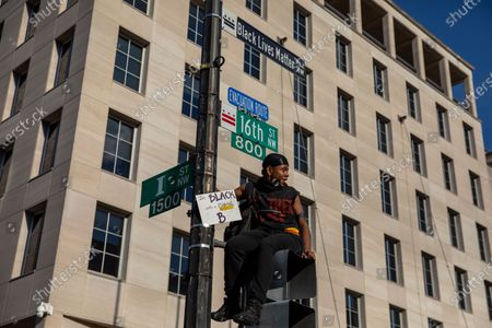 A man sits on a street signal during a march against police brutality and racism