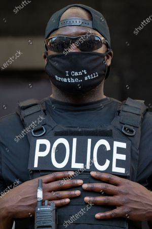 A member of the D.C. police force only identified as Officer Stewart stands outs of AFL-CIO headquarters during a march against police brutality and racism
