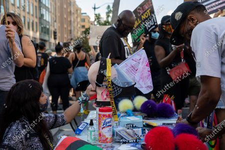 A woman sells PPE and protest accessories during a march against police brutality and racism