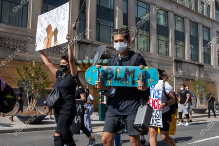 A protester carries a skateboard during a march against police brutality and racism