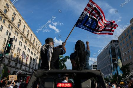 Protesters ride a Jeep during a march against police brutality and racism