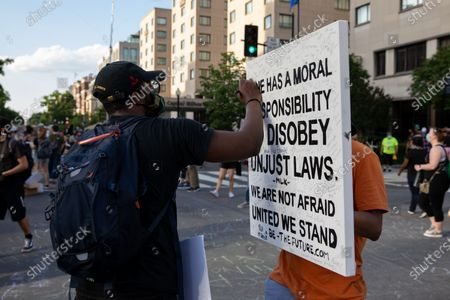 A man signs his name to a protesters's canvas during a march against police brutality and racism