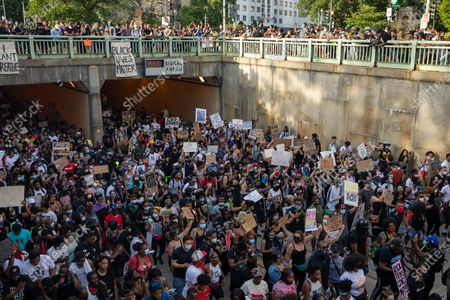 Protesters emerge from the tunnel beneath Scott Circle during a march against police brutality and racism