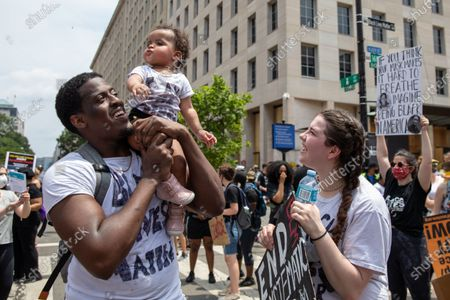 Nyron Dancy holds up his 1-year-old daughter Ny'omi Dancy, while her mother Kendal Gonthier looks on during a march against police brutality and racism