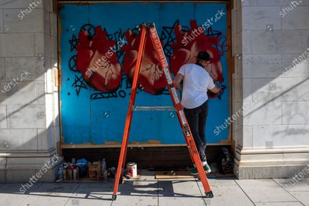 Artist Richshaad Ryan paints a mural on a boarded up window during a march against police brutality and racism