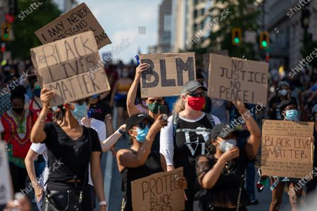 Protesters carry signs during a march against police brutality and racism