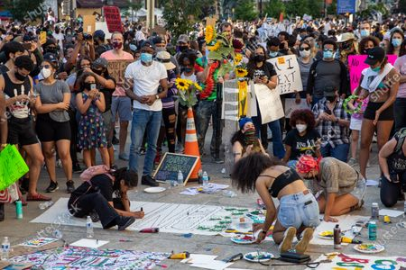 Protesters decorate signs during a march against police brutality and racism