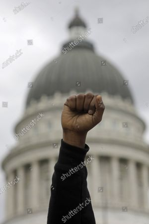 Protester raises his fist as people gather to remember Bernardo Palacios-Carbajal during a vigil at the Utah State Capitol, in Salt Lake City. People gathered, chanted and spoke out against racism and police brutality in front of the Utah Capitol, in an eighth straight day of protests in Salt Lake City. Rain started to come down as organizers set up a vigil for Bernardo Palacios-Carbajal, a 22-year-old man who was shot and killed by Salt Lake City police two weeks ago