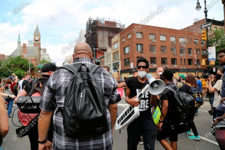 Jon Batiste, carrying an instrument and megaphone, bandleader on The Late Show with Stephen Colbert, participates in a march, in New York. Demonstrations continue across the United States in protest of racism and police brutality, sparked by the May 25 death of George Floyd in police custody in Minneapolis