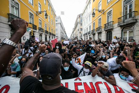 """Protesters hold up their fists while shouting slogans during the demonstration. Thousands of people gathered in Lisbon to demonstrate against racism in solidarity with the movement """"Black Lives Matter"""" following the death of George Floyd in the USA."""