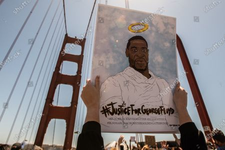 A sign honoring George Floyd is held up on the Golden Gate Bridge after the death of George Floyd. Protestors climbed over the rails and demonstrated in the lanes causing a shutdown of South Bound traffic.