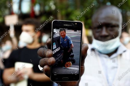 A protester shows a photo montage on his smartphone in which China's President Xi Jinping (up) is with his knee on US President Donald Trump's (down) neck during the protest gathering to protest against George Floyd's death in Minneapolis, in front of the US Embassy in Madrid, Spain, 07 June 2020. A bystander's video posted online on 25 May, appeared to show George Floyd, 46, pleading with arresting officers that he couldn't breathe as an officer knelt on his neck. The unarmed black man later died in police custody.