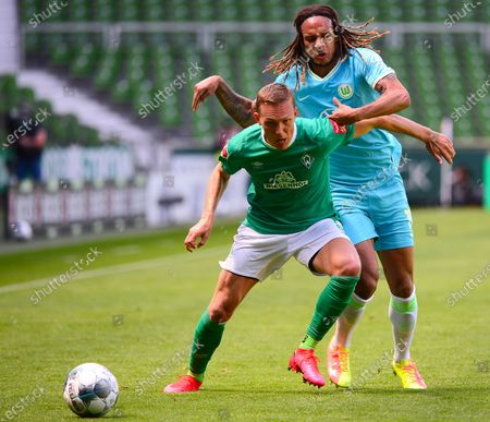 Bremen's Ludwig Augustinsson (L) in action against Wolfsburg's Kevin Mbabu (R) during the German Bundesliga soccer match between Werder Bremen and VfL Wolfsburg in Bremen, northern Germany, 07 June 2020.