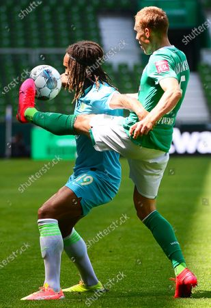 Bremen's Ludwig Augustinsson (R) in action against Wolfsburg's Kevin Mbabu (L) during the German Bundesliga soccer match between Werder Bremen and VfL Wolfsburg in Bremen, northern Germany, 07 June 2020.
