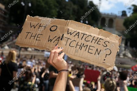 """A woman holds a sign """"who watch the watchmen"""" as in the comic wrote by Alan Moore during a Black Lives Matter protest on June 07, 2020 in Rome, Italy.The death of an African-American man, George Floyd, while in the custody of Minneapolis police has sparked protests and demonstrations of solidarity in many countries around the world."""