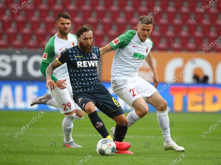 FC Augsburg's Alfred Finnbogason in action with FC Cologne's Marco Hoger (L) during the German Bundesliga soccer match between FC Augsburg and FC Cologne in Augsburg, Germany, 07 June 2020.
