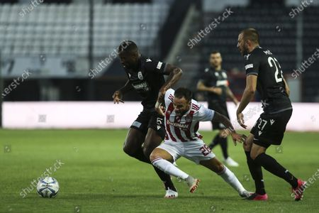 Olympiakos' Carlos Miguel Ribeiro Dias (Cafú), center, struggles for the ball between PAOK's Josip Misic, right, and Fernando Lopes dos Santos Varela, during a Super League soccer match, in Thessaloniki, northern Greece, . The Greek Super League returned this weekend, following almost three months of inactivity due to the coronavirus pandemic