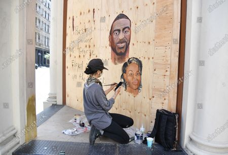 Artist Dina Paige Fischer paints a mural of George Floyd and Breonna Taylor on plywood that was put up after stores were vandalized in looted in the SoHo neighborhood of New York City.