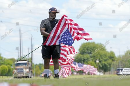 Stock Image of Bryan Smart plants American flags along Hillcroft Ave. as he walks toward The Fountain of Praise church, in Houston. A public memorial and private funeral service for George Floyd will be held at the church. Floyd died after being restrained by Minneapolis Police officers on Memorial Day