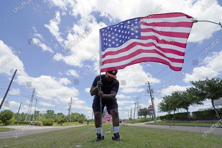 Stock Photo of Bryan Smart plants United States flags along Hillcroft Avenue as he walks toward The Fountain of Praise church, in Houston. A public memorial and private funeral service for George Floyd will be held at the church. Floyd died after being restrained by Minneapolis police officers on May 25