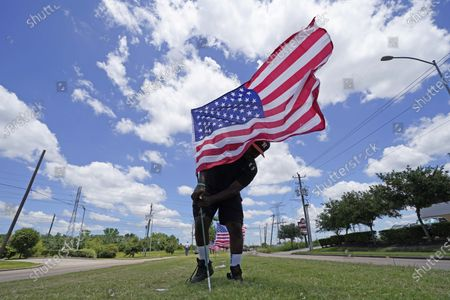 Bryan Smart plants United States flags along Hillcroft Avenue as he walks toward The Fountain of Praise church, in Houston. A public memorial and private funeral service for George Floyd will be held at the church. Floyd died after being restrained by Minneapolis police officers on May 25