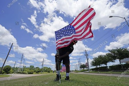 Bryan Smart plants American flags along Hillcroft Ave. as he walks toward The Fountain of Praise church, in Houston. A public memorial and private funeral service for George Floyd will be held at the church. Floyd died after being restrained by Minneapolis Police officers on Memorial Day