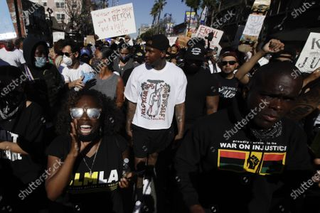 Demonstrators, including rapper YG, center in white, march in the Hollywood area of Los Angeles, during a protest over the death of George Floyd who died May 25 after he was restrained by Minneapolis police