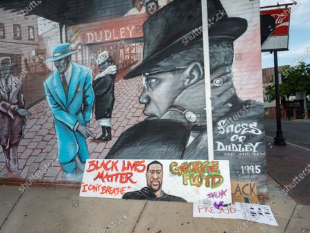 Boston, Massachusetts, USA: Black Lives Matter poster tribute to George Floyd in front of a mural of Malcolm X in Boston.