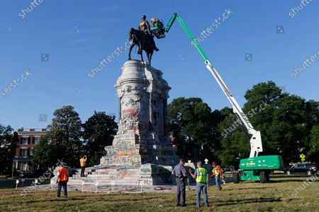 An inspection crew from the Virginia Department of General Services inspect the statue of Confederate Gen. Robert E. Lee on Monument Avenue, in Richmond, Va. Virginia Gov. Ralph Northam has ordered the removal of the statue