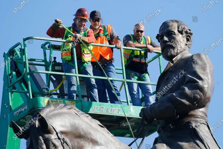 An inspection crew from the Virginia Department of General Services takes measurements as they inspect the statue of Confederate Gen. Robert E. Lee on Monument Avenue, in Richmond, Va. Virginia Gov. Ralph Northam has ordered the removal of the statue